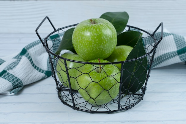 Green apples with leaves in the metallic black basket placed on white surface.  .