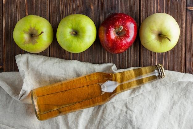 Mele verdi con una rossa e vista superiore del succo di mele su un panno e su un fondo di legno