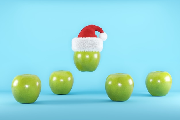 Green apples with santa hat floating on blue
