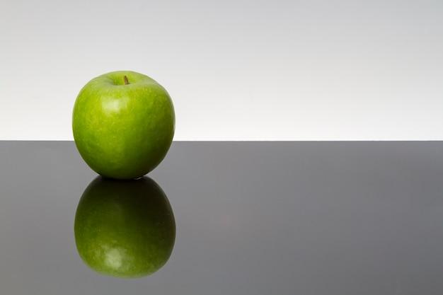 暗い背景に分離された反射テーブルに水滴と緑のリンゴ。コピースペース。鏡面。