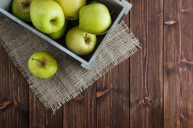 Le mele verdi in un piano della scatola di legno pongono su una tela di sacco e su un fondo di legno