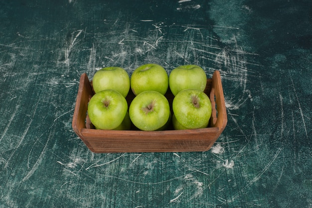 Green apples in wooden box on marble surface.