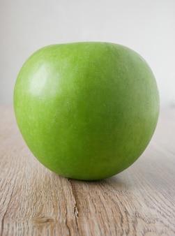Green apples on the wooden floor