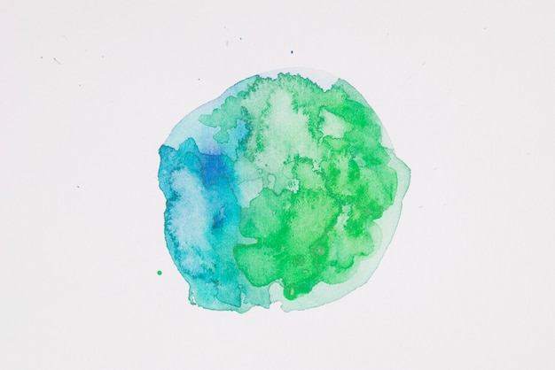 Green and aquamarine paints in form of circle on white paper