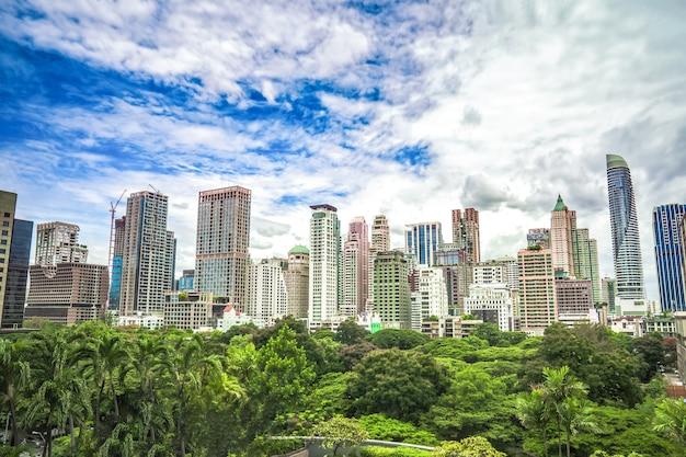 탁 트인 하늘에 높은 건물이있는 방콕 대도시 한복판의 녹지대.