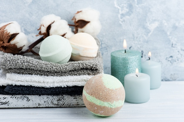 Green aroma bath bombs in spa composition with dry flowers and towels