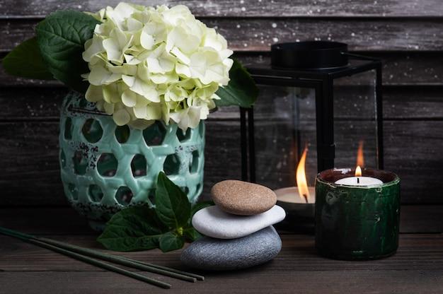 Зеленые ароматические палочки в спа-натюрмортах с цветами гортензии и зажженными свечами