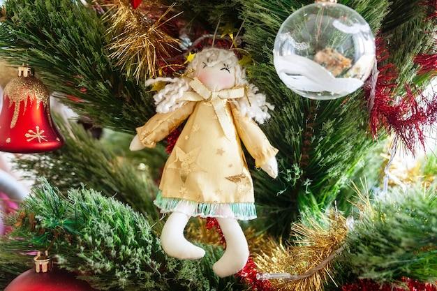 天使のおもちゃで飾られた緑の人工的なクリスマスツリー