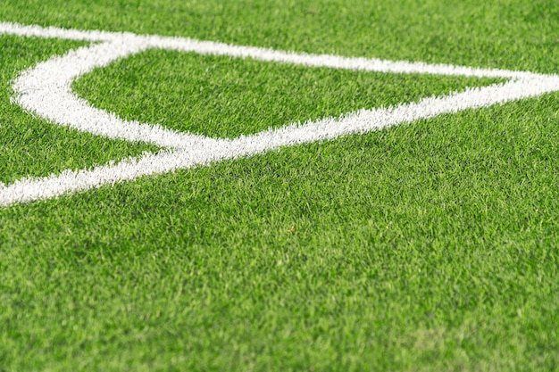 Green artificial grass turf soccer football field background with white corner line boundary. top view