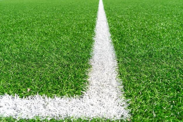 Зеленая искусственная трава газон футбол футбольное поле фон с белой линией границы.