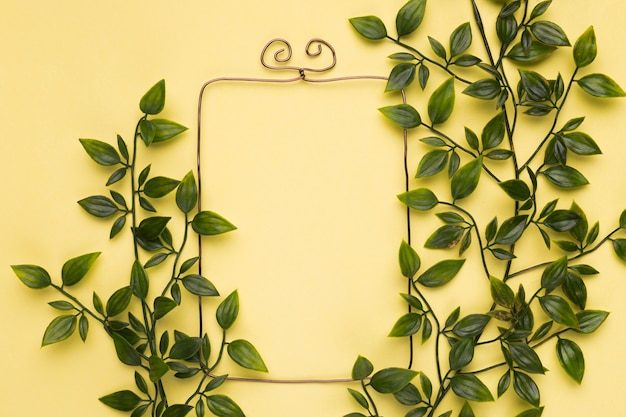 Green artificial leaves near the empty frame on yellow backdrop