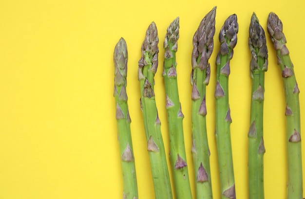 밝은 노란색 테이블에 그린 아스파라거스입니다. 봄의 제철 야채.