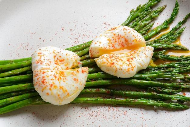 皿の上のポーチドエッグとグリーンアスパラガス