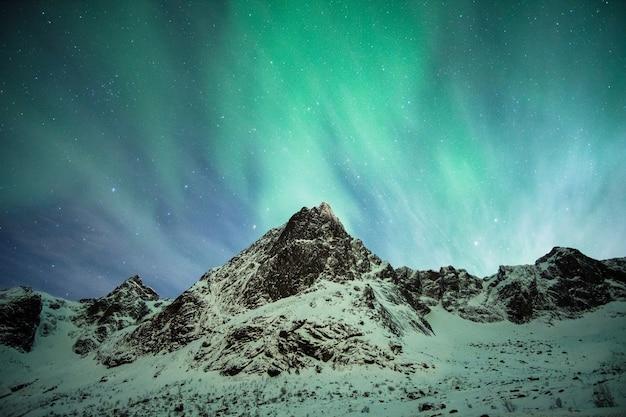 ロフォーテン諸島の雪山での緑のオーロラ爆発
