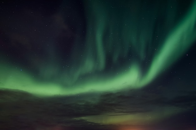 Green aurora borealis, northern lights dancing in the night sky