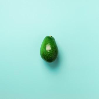 파란색 배경에 녹색 아보카도입니다. 평면도. 팝 아트 디자인, 창의적인 여름 음식 개념.