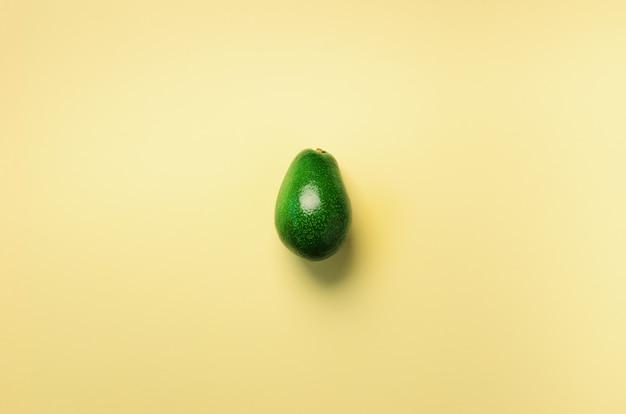 노란색 배경에 녹색 아보카도입니다. 팝 아트 디자인, 창의적인 여름 음식 개념. 최소한의 평평한 평신도 스타일.