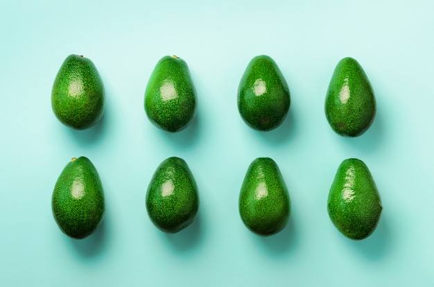 파란색 배경에 녹색 아보카도 패턴입니다. 최소한의 평평한 평신도 스타일의 유기농 아보카도.