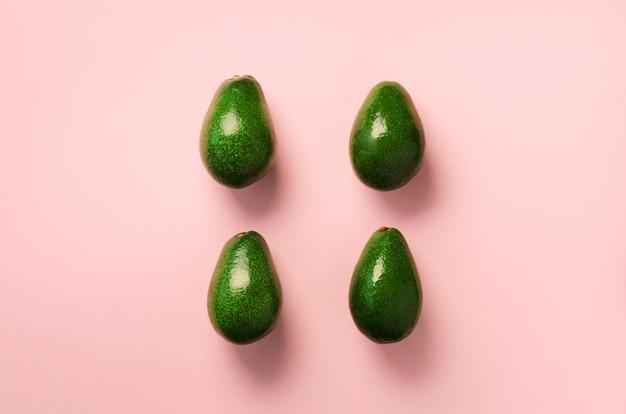 분홍색 배경에 녹색 아보카도 패턴입니다. 최소한의 평평한 평신도 스타일의 유기농 아보카도.