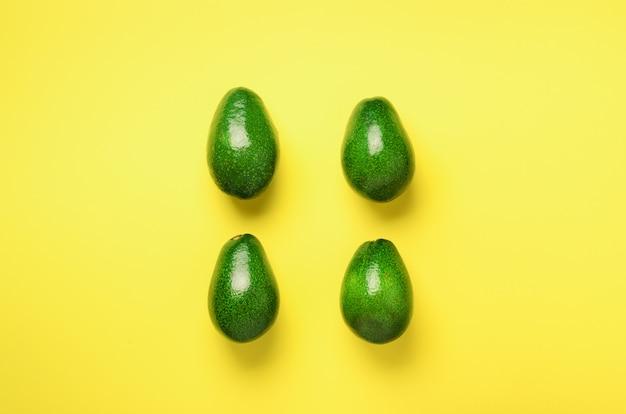 노란색 바탕에 녹색 아보카도 패턴입니다. 평면도. 팝 아트 디자인, 창의적인 여름 음식 개념. 최소한의 평평한 평신도 스타일의 유기농 아보카도.