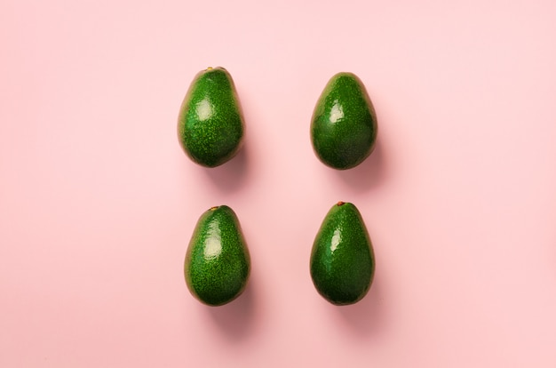 Green avocado pattern on pink background. organic avocadoes in minimal flat lay style.