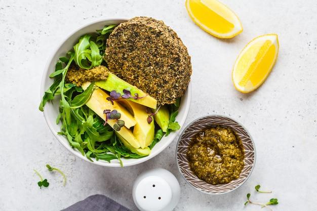 Green avocado salad with green vegan cutlet, arugula and pesto in gray bowl. healthy vegan food concept.