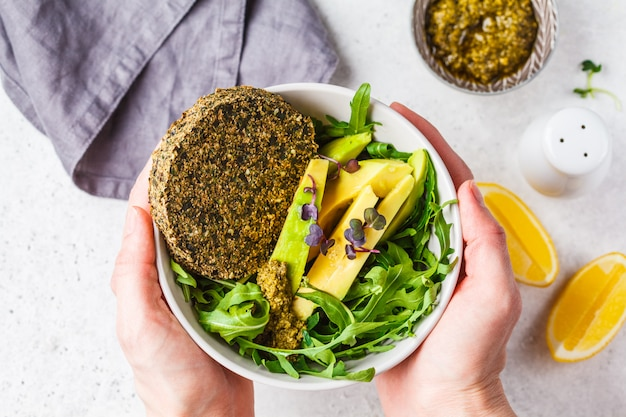 Green avocado salad with green vegan cutlet, arugula and pesto in hand. healthy vegan food concept.