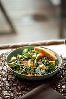Салат из зеленого авокадо с тостами на столе в ресторане