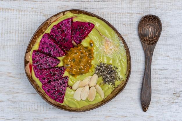 Зеленый смузи из авокадо в кокосовой чаше с драконьим фруктом, маракуйей, миндальными хлопьями, кокосовой стружкой и семенами чиа на завтрак, крупным планом. концепция здорового питания, суперпродукта. бали, индонезия