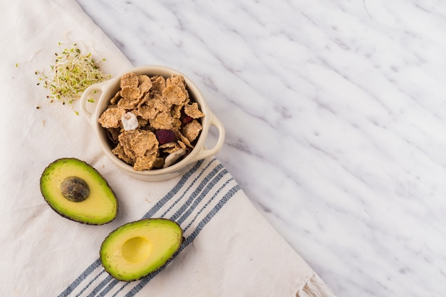 Зеленый авокадо с хлопьями в миске на столе