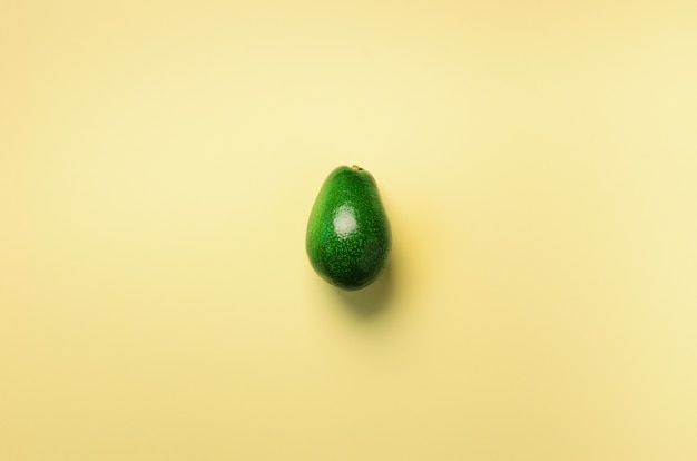 Green avocado on yellow background. pop art design, creative summer food concept. minimal flat lay style.