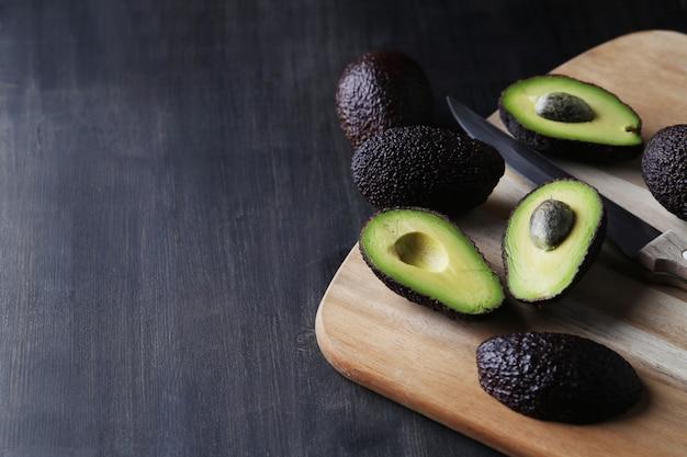 Зеленые авокадо на разделочной доске