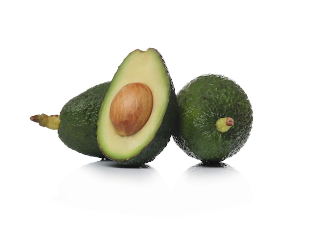 Green avocados on a white surface