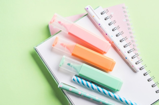 Green back to school flat lay with pastel stationery