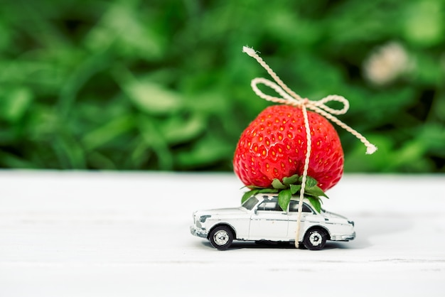 On a green background a small toy car with red strawberries place inscription