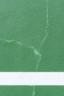 Green background. sport wall with cracked paint.