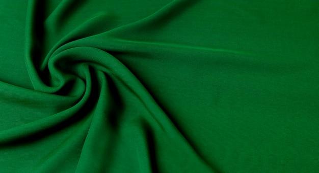 Зеленый фон с текстурой натуральной хлопковой ткани, уложенной волнами.