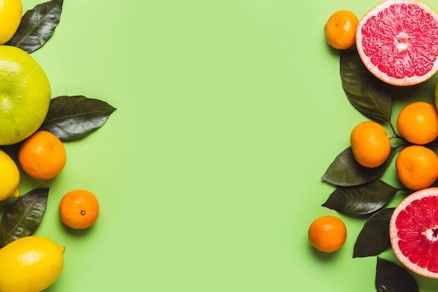 さまざまな柑橘系の果物と緑の背景。健康食品のコンセプト。