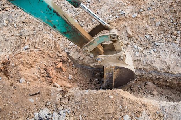 Green backhoe dredging soil earth