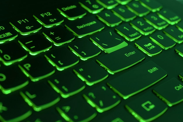 Green backlit laptop keyboard, hacking and blockchain concept