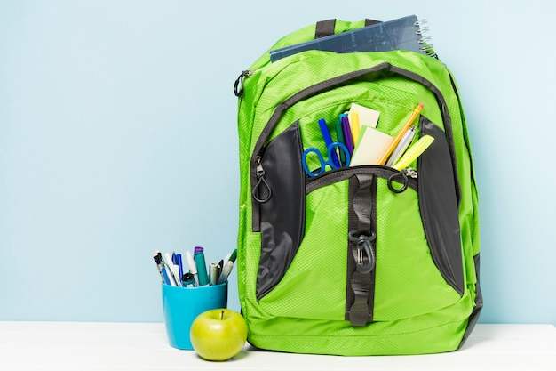 Green backpack with school accessories