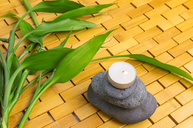 Green bamboo branches and black stone pyramid with lighting candle on wooden mat
