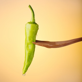Green banana pepper on orange background