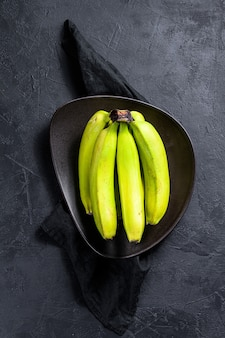 Green bananas on a plate. black background. top view. space for text. tropical fruit