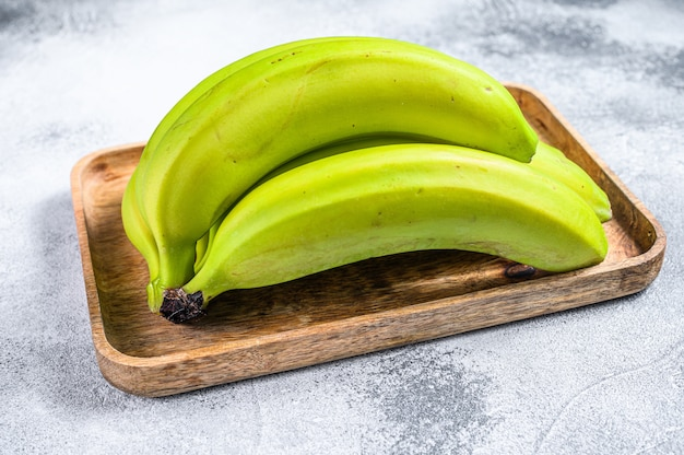 Green bananas on a wooden tray. gray background. top view. tropical fruit