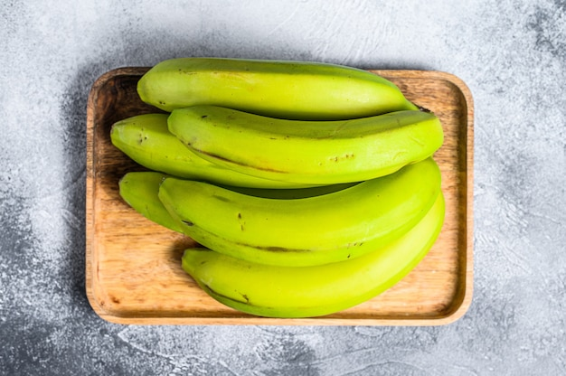 Green bananas on a wooden tray. top view. tropical fruit