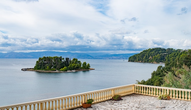 Green bay with crystal water on corfu island. beautiful landscape of ionian sea beach, view from hotel with fence on balcony on small island in water.