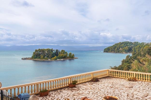 코르푸 섬에 크리스탈 물으로 그린 베이. 이오니아 바다 해변의 아름 다운 풍경, 물에 작은 섬에 발코니에 울타리와 함께 호텔에서 볼 수 있습니다.