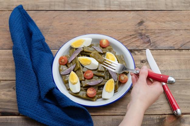 Салат из зеленой фасоли с вареным яйцом и помидорами. женская рука ест салат. скопируйте пространство. деревянная поверхность.