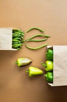 Зеленые бобы и перец в ремесленной упаковке на коричневом столе. собирайте органическую здоровую пищу